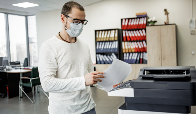 Man wearing a face mask handles printer documents